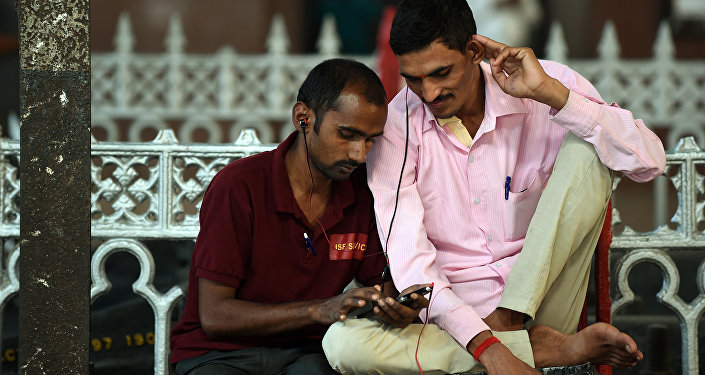 Indian commuters use their smartphones following the introduction of a new free Wi-Fi Internet service in Mumbai's central railway station on January 22, 2016