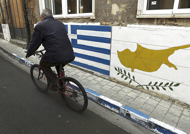 A man passes with a bicycle outside of a Greek Cypriot guard post with Cyprus', right, and Greece' flags painted on the wall in central divided capital Nicosia in the eastern Mediterranean island of Cyprus, on Thursday, Feb. 16, 2017