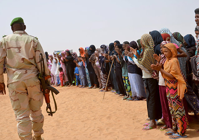 A Niger soldier walk past Malian refugees (File)