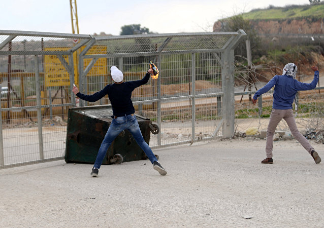 A Palestinian protester hurls a molotov cocktail towards Israeli troops during clashes near Israel's Ofer Prison near the West Bank city of Ramallah, March 7, 2017
