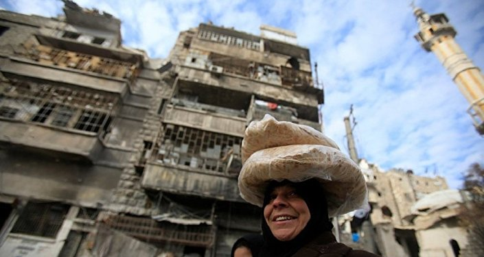 Syrian woman carries bags of bread on her head at the one of the street in Aleppo