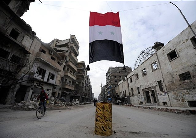 A Syrian national flag hangs in a damaged neighbourhood in Aleppo, Syria