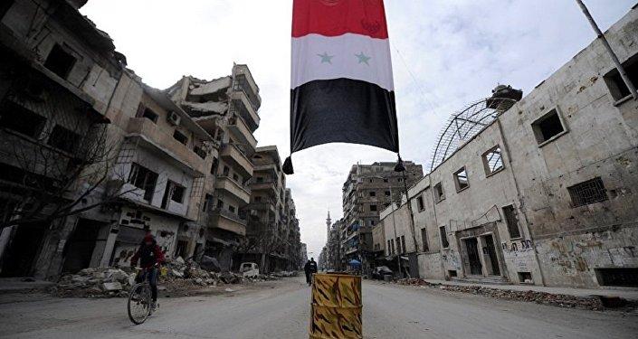 A Syrian national flag hangs in a damaged neighbourhood in Aleppo, Syria