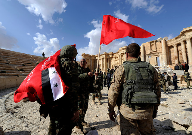 Syrian army soldiers carry flags in the amphitheater of the historic city of Palmyra, Syria March 4, 2017.