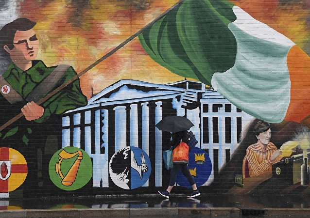 A woman walks past a political mural in the Falls Road area of west Belfast, Northern Ireland, February 28, 2017.
