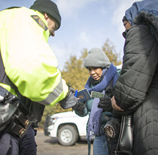 An RCMP officer checks the documents of two women from Sudan after they illegally crossed the Canada-US border. (File)