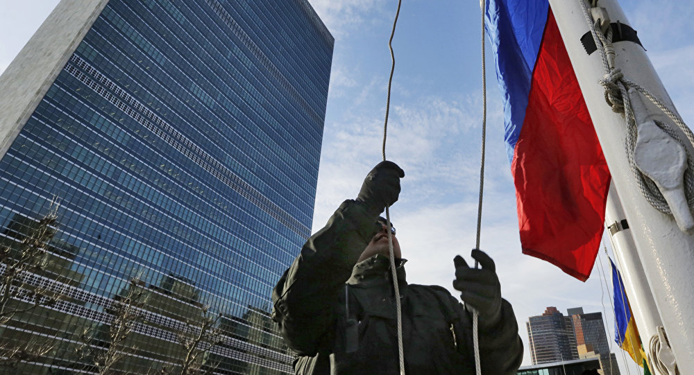 A United Nations security officer raises the Russian flag outside U.N. headquarters, Tuesday morning, Feb. 21, 2017