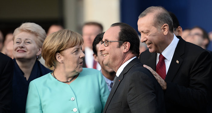 (L-R) German Chancellor Angela Merkel, French President Francois Hollande and Turkish President Recep Tayyip Erdogan share a smile as they attend the fly-past of NATO countries' jetfighters at the entrance of the National Stadium, the venue of the starting NATO summit, on July 8, 2016