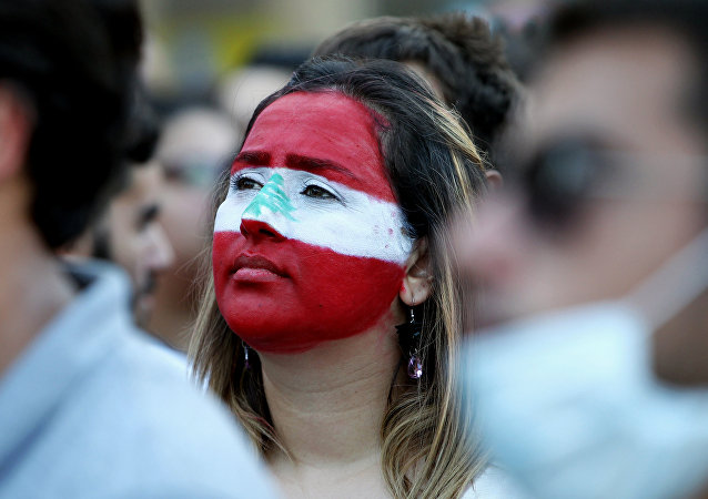 A Lebanese woman, with her face painted in the colours of Lebanon's national flag, takes part in a demonstration in downtown Beirut on August 8, 2015