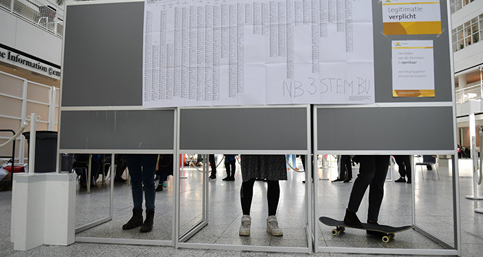People prepare their ballots to vote in the Dutch general elections in The Hague on March 15, 2017