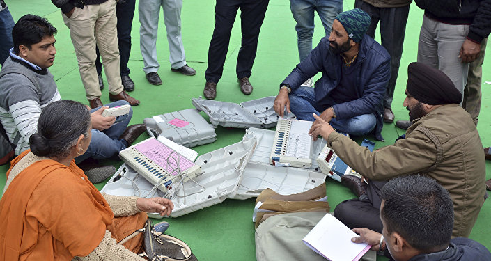 Election officials examine Electronic Voting Machines (EVM) on the eve of Punjab state elections at a distribution centre in Amritsar, India, Friday, Feb. 3, 2017