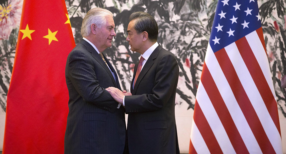 U.S. Secretary of State Rex Tillerson, left, and Chinese Foreign Minister Wang Yi stare at each other as they shake hands at the end of a joint press conference following their meeting at the Diaoyutai State Guesthouse in Beijing, China, Saturday, March 18, 2017