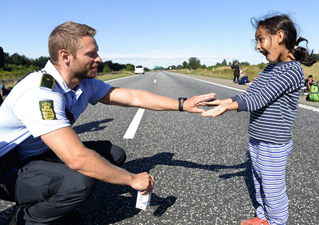 Danish policeman plays with a migrant girl (file)