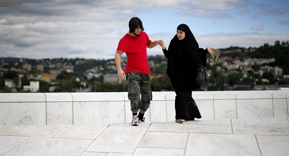 A man helps a woman up a step on the roof of the Opera house in Oslo on August 11 , 2011