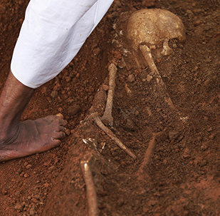 In this Jan 2, 2013 photo, a hospital worker walks by a partially excavated skeleton, at a mass grave found inside the premises of a government hospital in Matale, about 140 kilometers (about 88 miles) north east of Colombo, Sri Lanka.