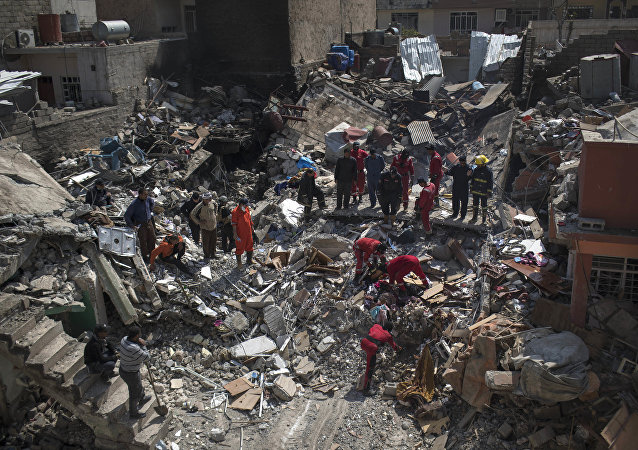 Civil protection rescue team work on the debris of a destroyed house to recover the body of people killed during fights between Iraq security forces and Islamic State on the western side of Mosul, Iraq, Friday, March 24, 2017