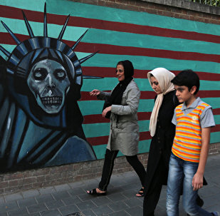 An Iranian family walks past anti-US graffiti on the wall of the former US embassy in Tehran on July 14, 2015