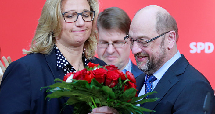 Social Democratic Party (SPD) leader Martin Schulz presents flowers to Anke Rehlinger, top candidate in the Saarland state elections, at the SPD headquarters in Berlin, Germany, March 27, 2017