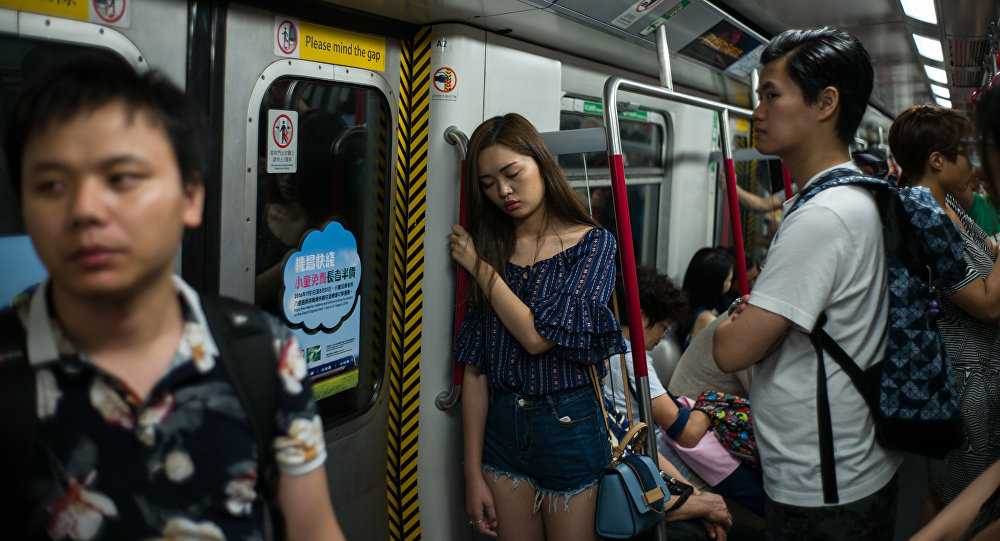 A woman sleeps as she stands during her commute on an underground MTR train in Hong Kong on July 18, 2016