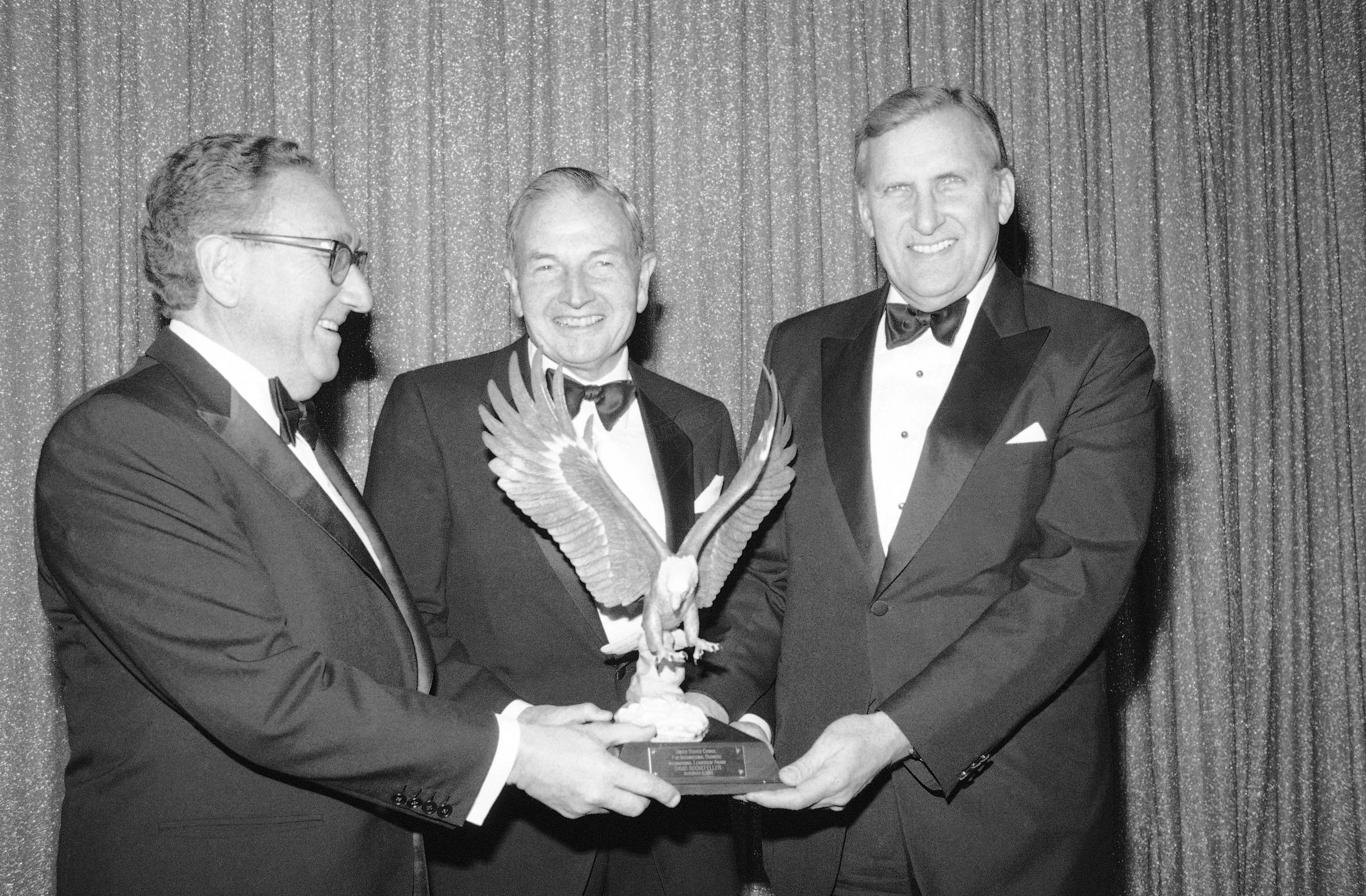 David Rockefeller, center, chairman of the Chase Manhattan's Bank's International Advisory Committee and the banks former chairman of the board and chief executive officer, receives the 1983 International Leadership Award from the U.S. Council for International Business, presented by Dr. Henry A. Kissinger, former Secretary of State, left, and Ralph A. Pfeiffer, Jr., U.S. Council Chairman, at New York's Pierre Hotel on Thursday, Dec. 9, 1983. The award recognizes outstanding contributions to world trade and investment.