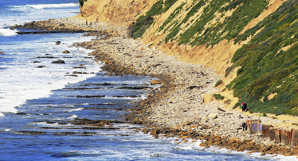In this Sunday, March 26, 2017, photo, waves roll onto boulders at the foot of a sea cliff near Royal Palms Beach in the San Pedro area of Los Angeles.