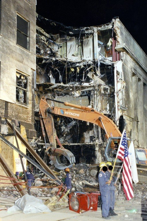 A worker holds up an American flag as a crane excavates through the devastated Pentagon.