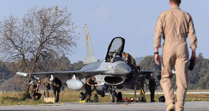 A Belgian pilot walks toward his F-16 fighter jet