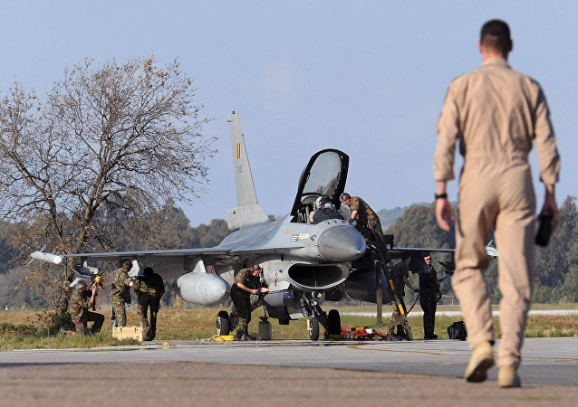 A Belgian pilot walks toward his F-16 fighter jet