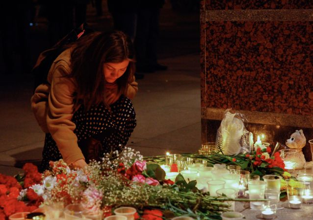 A girl lights a candle at the entrance to Spasskaya metro station in St. Petersburg in memory of the victims of the metro train blast
