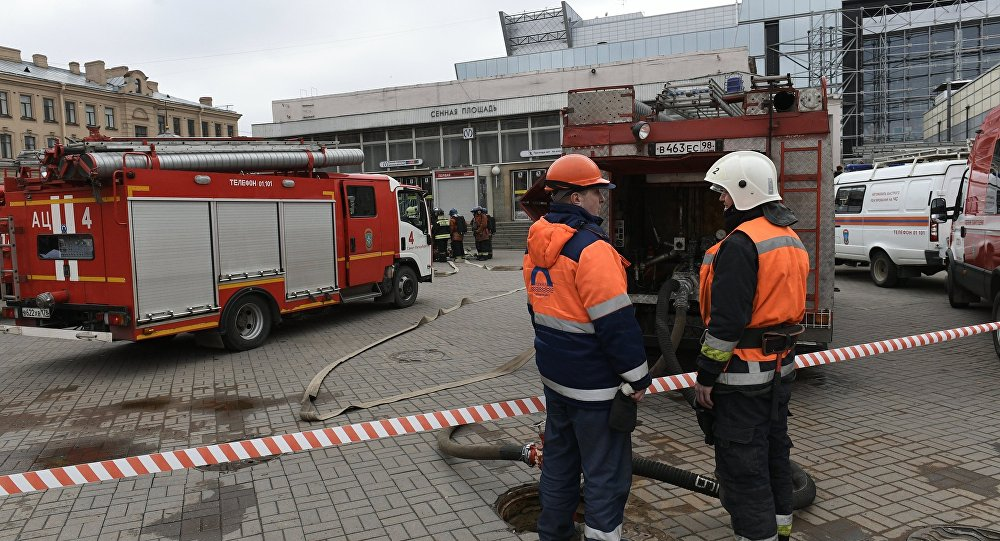Fire-fighters from the fire-prevention service of the Russian Ministry for Civil Defense, Emergencies and Disaster Relief stand near Sennaya Ploshchad metro station that has been closed after an anonymous bomb scare