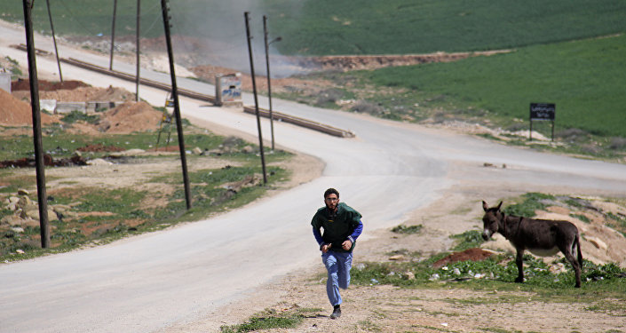 A Syrian medic runs for cover during the air strikes which hit a hospital in Khan Sheikhun, a rebel-held town in the northwestern Syrian Idlib province, on April 4, 2017