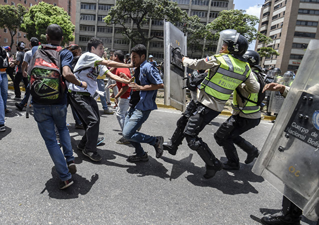 Venezuela's opposition activists clash with riot police agents during a protest against Nicolas Maduro's government in Caracas on April 4, 2017