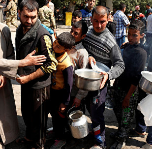Civilians queue to collect food during food delivery in Western Mosul, Iraq March 30, 2017