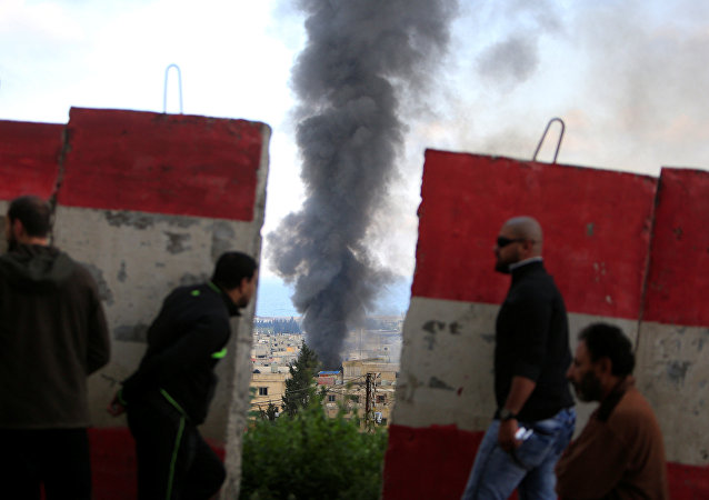 People stand behind a Lebanese Army barrier as smoke rises during clashes between Islamists and Palestinian Fatah gunmen in Ain al-Hilweh camp Palestinian refugee camp near Sidon, South Lebanon April 9, 2017