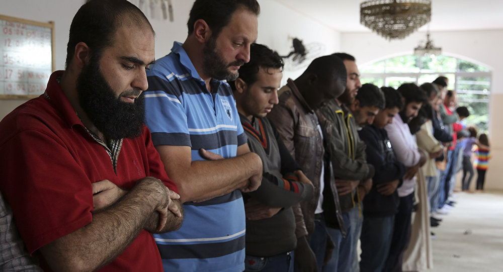 In this May 15, 2015 photo, Syrian refugee Abdulhannan Mouhammed, left, attends Friday prayer at a mosque in Sao Paulo, Brazil