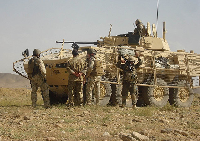 In this photograph taken on December 21, 2011, Polish soldiers with the NATO-led International Security Assistance Force (ISAF) stand guard after five of their comrades were killed when their armored military vehicle was hit by a roadside bomb in Ghazni province