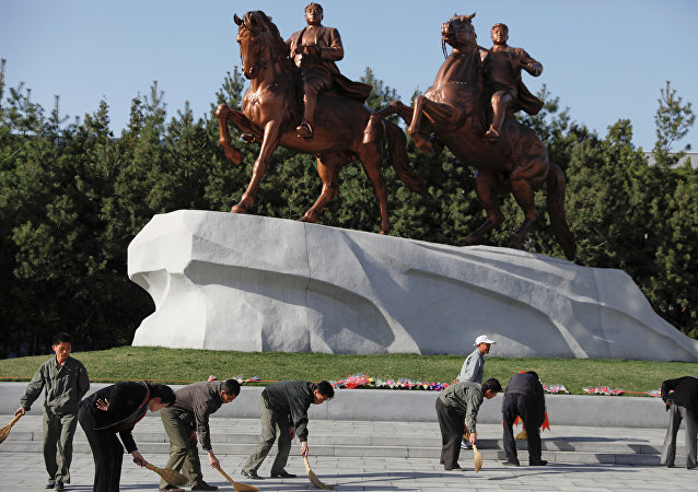 People sweep in front of statues of former North Korean leaders Kim Il Sung and Kim Jong Il in central Pyongyang, North Korea April 12, 2017.