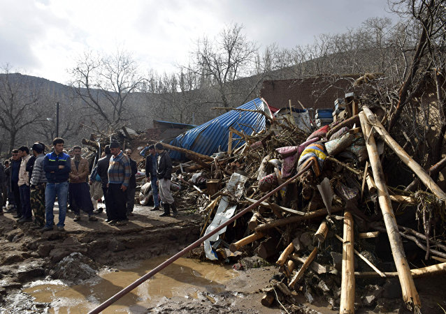 In this picture released by Islamic Republic News Agency, IRNA, villagers stand next to wreckages of buildings in Chenar village near city of Ajabshir in northwestern Iran, Saturday, April 15, 2017.