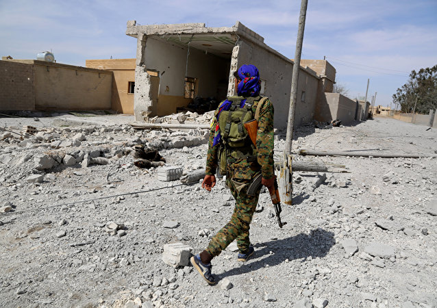 A member of the US-backed Syrian Democratic Forces (SDF), made up of an alliance of Arab and Kurdish fighters, patrols in the town of Al-Karamah, 26 kms from the Islamic State (IS) group bastion of Raqa, as they advance to encircle the jihadists, on March 26, 2017