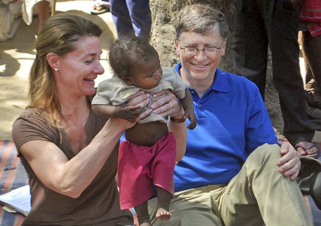 In this Wednesday, March 23, 2011 file photo, Microsoft Corp. founder and philanthropist Bill Gates, right, and his wife Melinda Gates attend to a child as they meet with members of the Mushar community at Jamsot Village near Patna, Indi