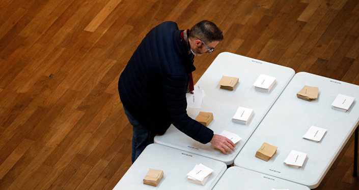 A man choose his ballots before voting in the first round of 2017 French presidential election at a polling station in Lyon, France, April 23, 2017.