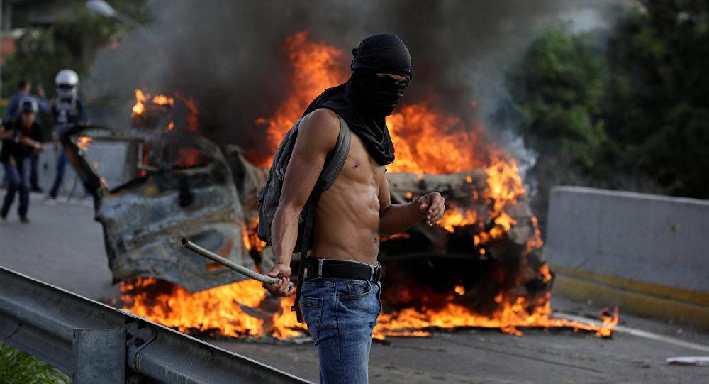 A demonstrator stands near fire during a rally against Venezuela's President Nicolas Maduro in Caracas, Venezuela April 24, 2017