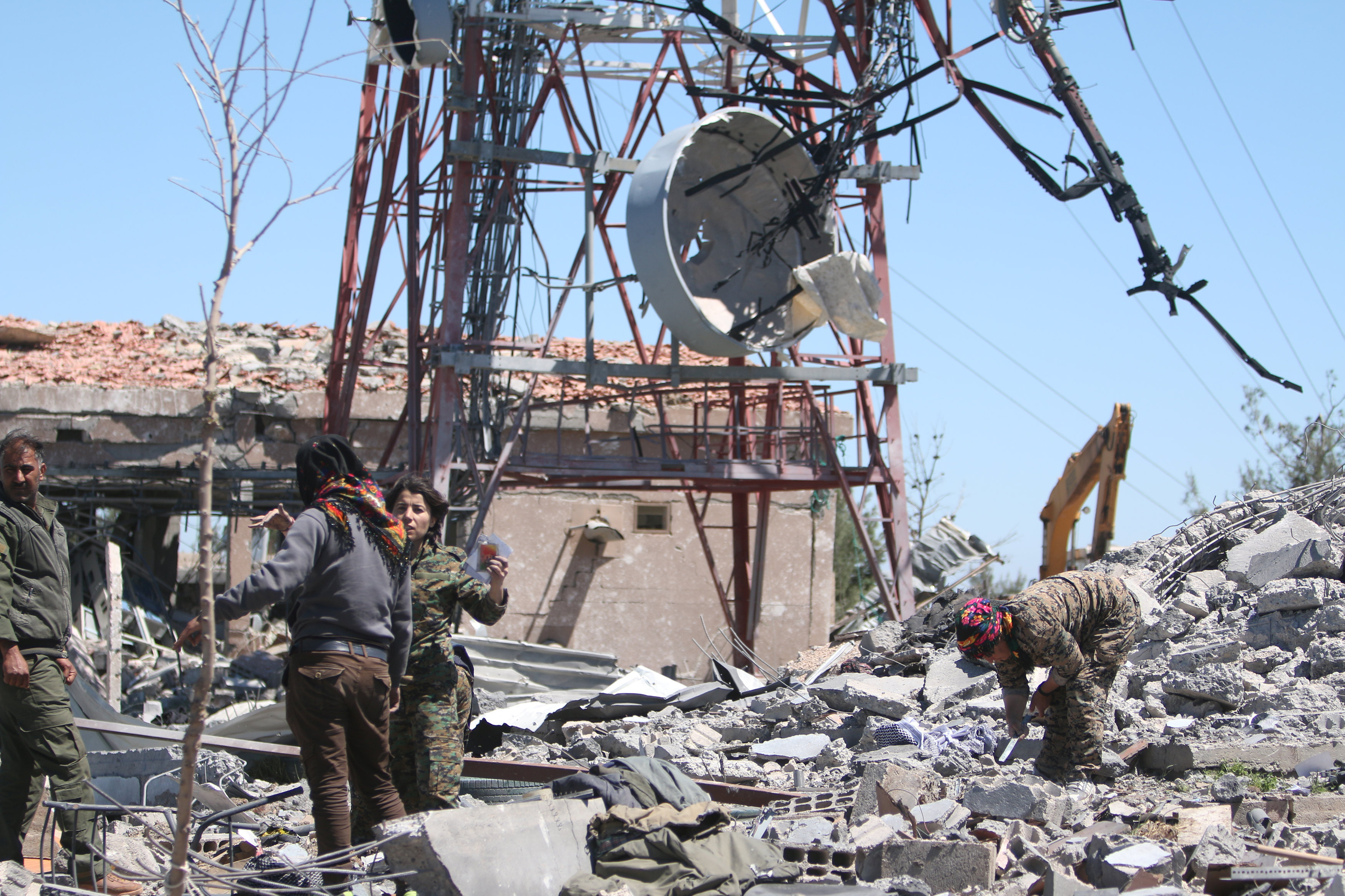 Fighters from the Kurdish People's Protection Units (YPG) inspect the damage at their headquarters after it was hit by Turkish airstrikes in Mount Karachok near Malikiya, Syria April 25, 2017