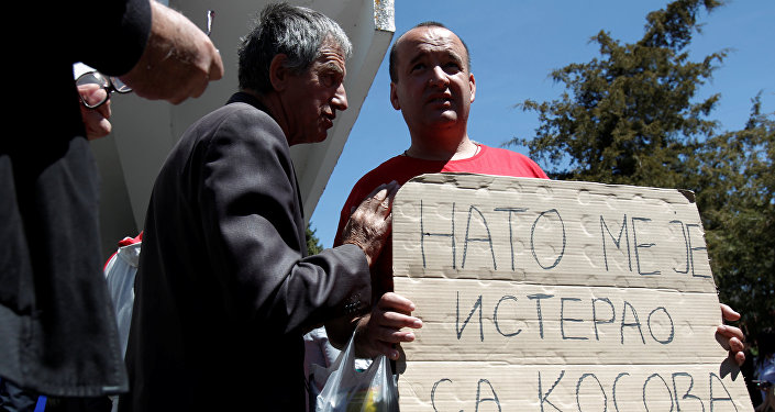 A protester holds a banner that reads NATO forced me out of Kosovo after a protest described as a parallel parliament, ahead of April 28's parliament vote to ratify the Montenegro's NATO membership, in the village of Murino, Montenegro, April 26, 2017