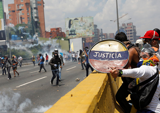 Opposition supporters use a shield reading Justice as they clash with security forces during a rally against Venezuela's President Nicolas Maduro in Caracas, Venezuela April 26, 2017