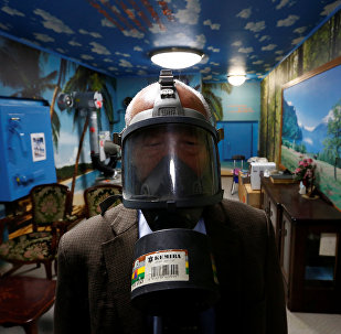 Seiichiro Nishimoto, CEO of Shelter Co., poses wearing a gas mask at a model room for the company's nuclear shelters in the basement of his house in Osaka, Japan April 26, 2017