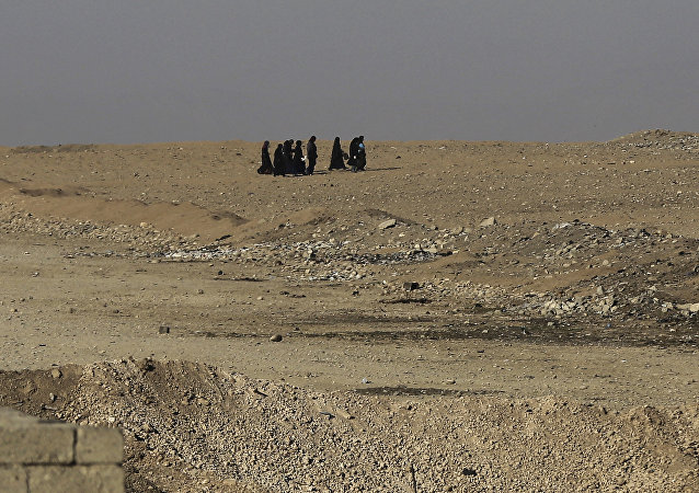 Iraqi citizens fleeing the fighting between Iraqi forces and Islamic State militants, walk in the desert as they try to reach a point where Iraqi forces transfer people from the the front line neighborhoods to refugee camps