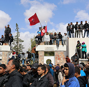 Tunisians wave their national flag as they take part in a general strike against marginalization and to demand development and employment on April 11, 2017, in Tataouine, south of Tunisia