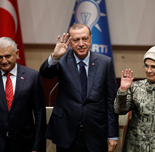 Turkish President Tayyip Erdogan greets his supporters after a speech as he is flanked by his wife Emine Erdogan and Prime Minister Binali Yildirim at the ruling AK Party's headquarters in Ankara, Turkey, May 2, 2017