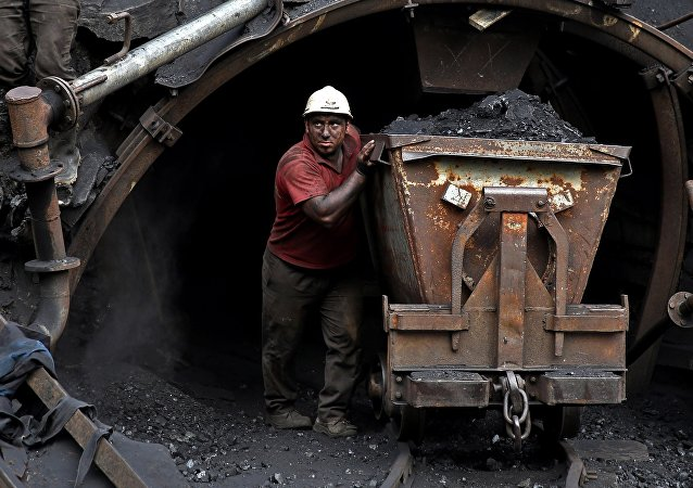 (File) In this Monday, Aug. 18, 2014 photo, an Iranian coal miner pushes a metal cart loaded with coal at a mine near the city of Zirab 212 kilometers (132 miles) northeast of the capital Tehran, on a mountain in Mazandaran province, Iran